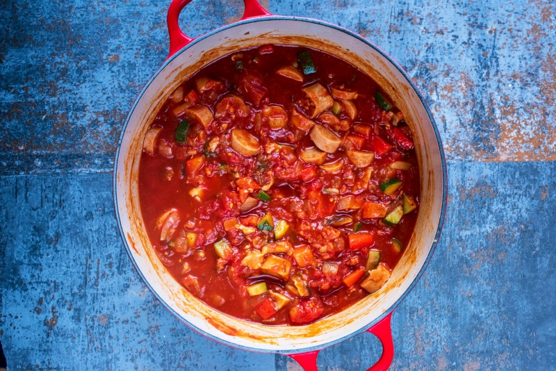 Chopped vegetables and sliced sausage in a tomato sauce cooking in a large red pan