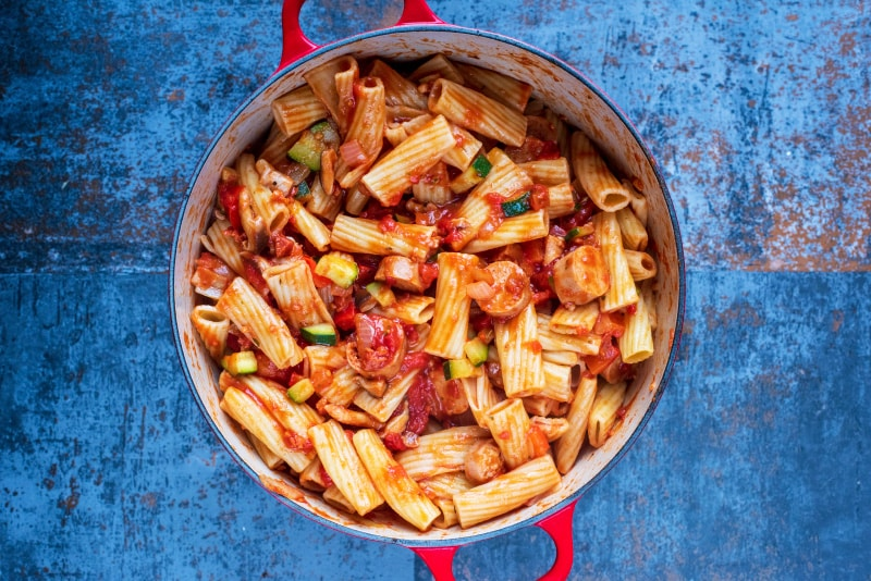 Chopped vegetables, sliced sausage and rigatoni pasta cooking in a large red pan