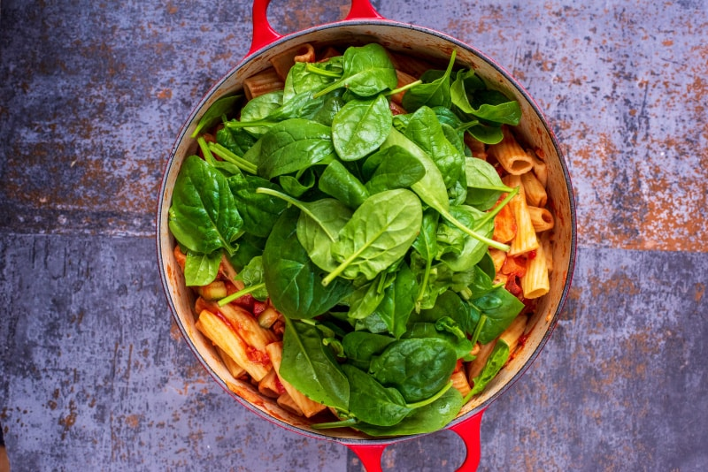Chopped vegetables, sliced sausage and rigatoni pasta cooking in a large red pan with a large pile of spinach in it