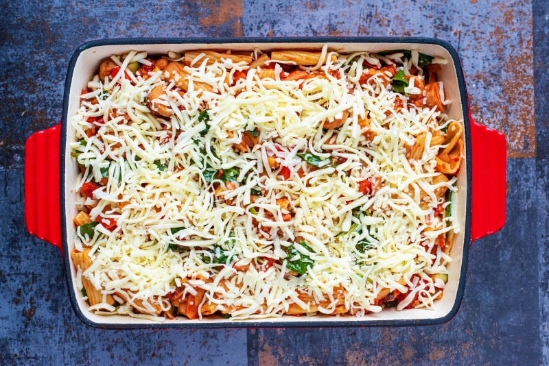A large red baking dish containing sausage pasta bake, covered with grated cheese