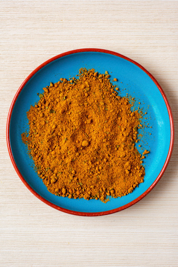 A blue plate with a spice blend on it
