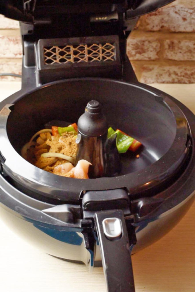 An air fryer with the lid open containing chicken, vegetables and spices