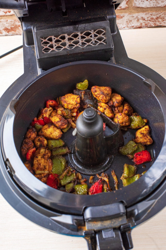 An air fryer with the lid open containing cooked chicken, vegetables and spices