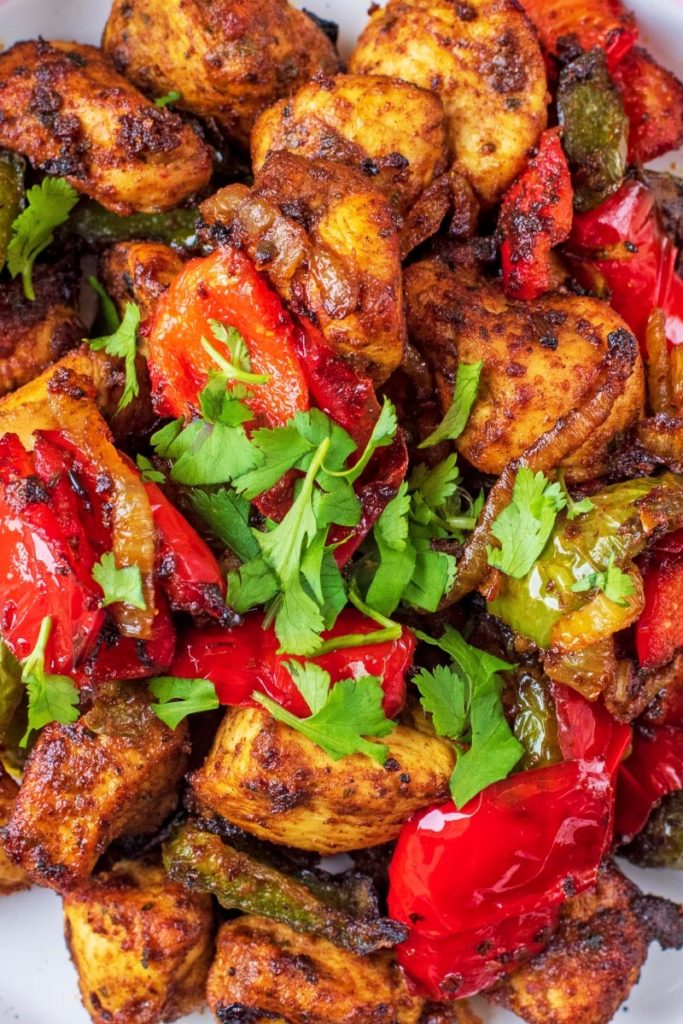 Chicken tikka and chopped vegetables covered in coriander