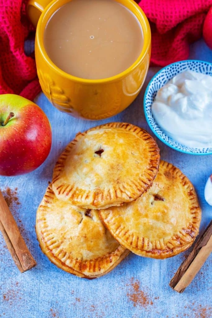 Apple pies next to a dish of yoghurt and a red towel