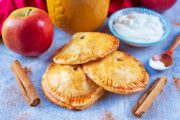 Three apple hand pies surrounded by an apple, cinnamon sticks, yoghurt and a cup of coffee