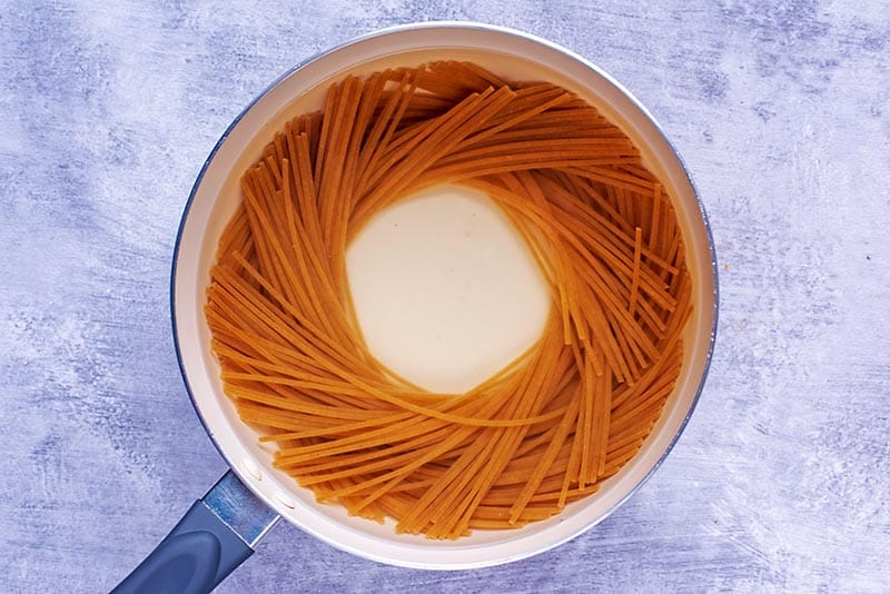 A saucepan with spaghetti cooking in it