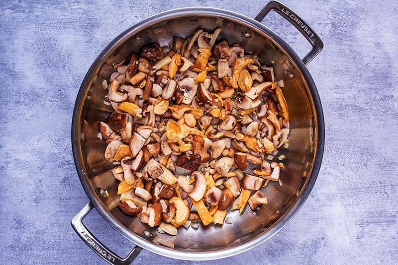 Sliced mushrooms cooking in a large pan