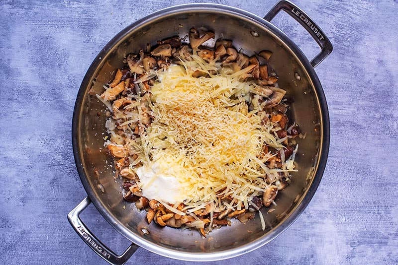 A large pan containing cooked mushrooms, cream and grated cheese