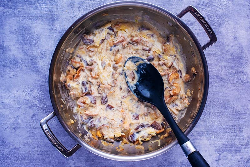 A creamy mushroom sauce cooking in a large pan