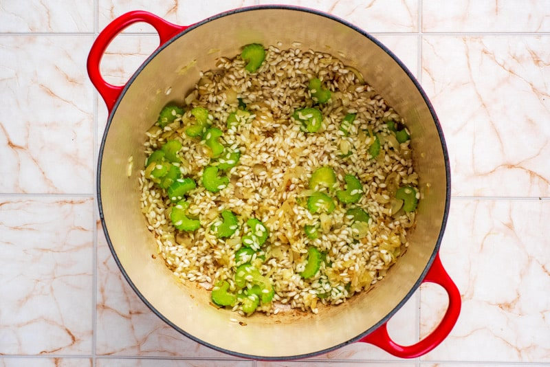 A large red pan containing celery, shallots and risotto rice