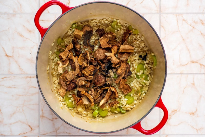 A large red pan containing celery, shallots, risotto rice and mushrooms