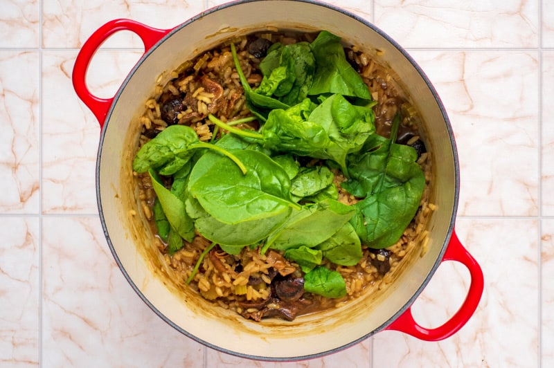 A large red pan containing celery, shallots, risotto rice and spinach