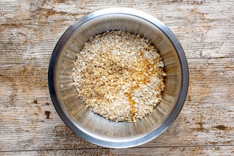 A mixing bowl containing rolled oats, coconut oil and maple syrup