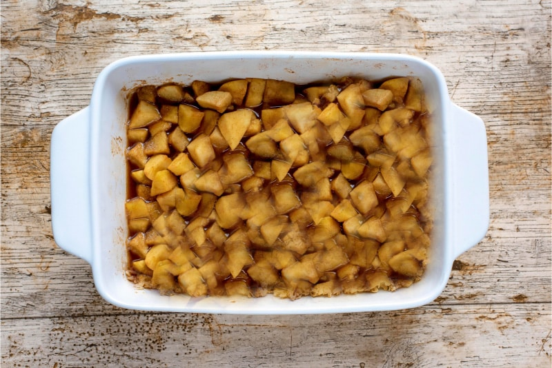 A white baking dish filled with cook chopped apples