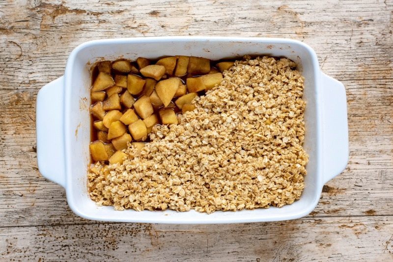 A white baking dish filled with cook chopped apples and topped with oats