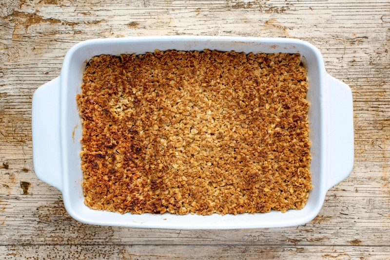 Oaty apple crumble with a browned top in a white baking dish