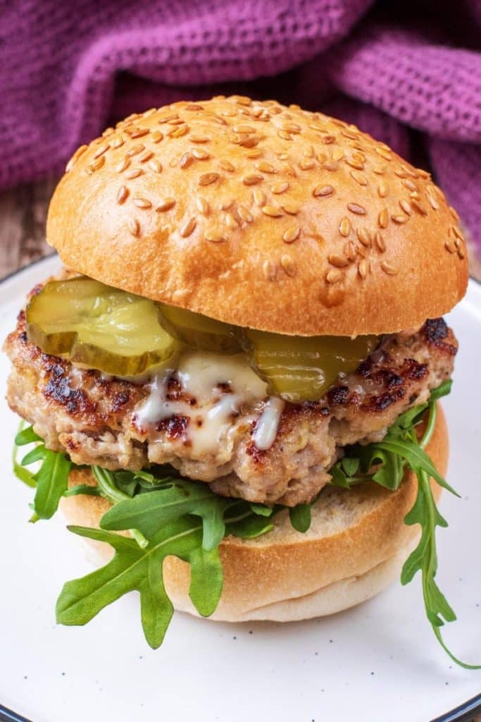 Pork burger, rocket, gherkins and cheese in a sesame bun