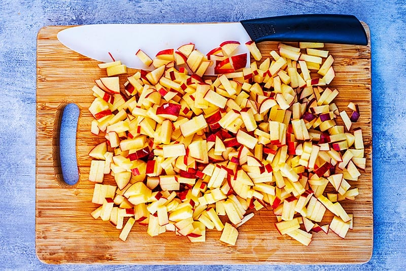 A wooden chopping board covered in tiny chunks of chopped apple