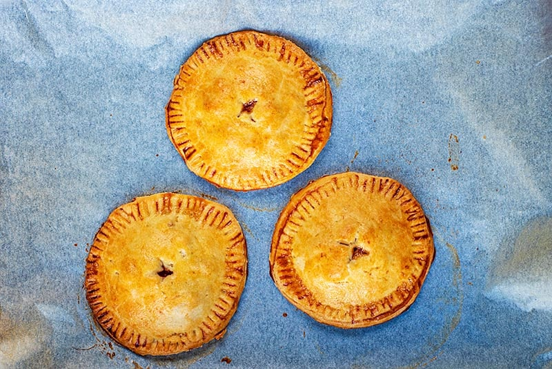 Three cooked hand pies on a baking sheet