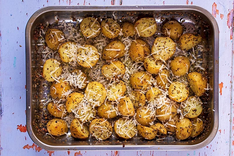 A roasting tin full of roasted potatoes covered in parmesan