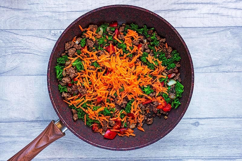 A frying pan with pepper, onion, garlic, carrot, kale and ground beef