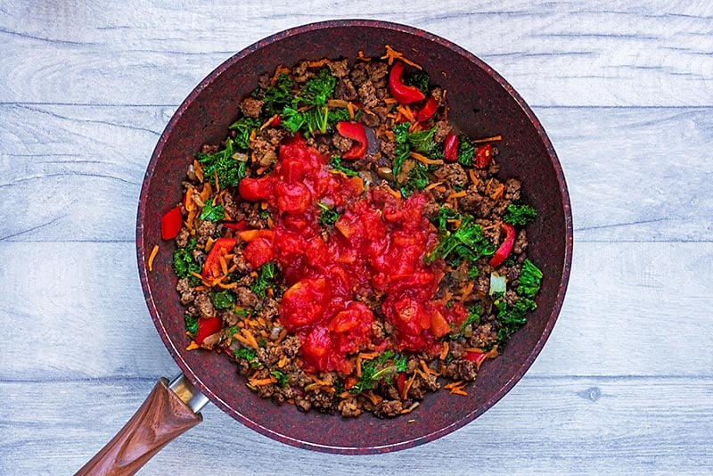 Grounf beef and vegetables cooking in a pan with chopped tomatoes