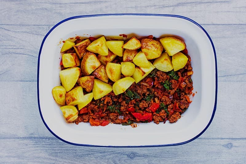 A baking dish filled with beef and vegetables and half topped with potatoes