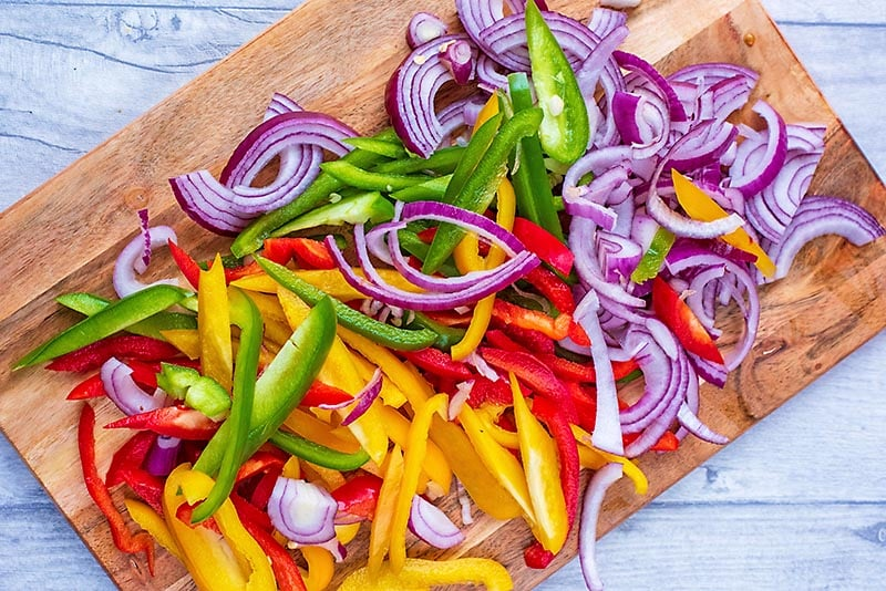 A wooden chopping board with trips of red and yellow bell pepper and sliced red onion
