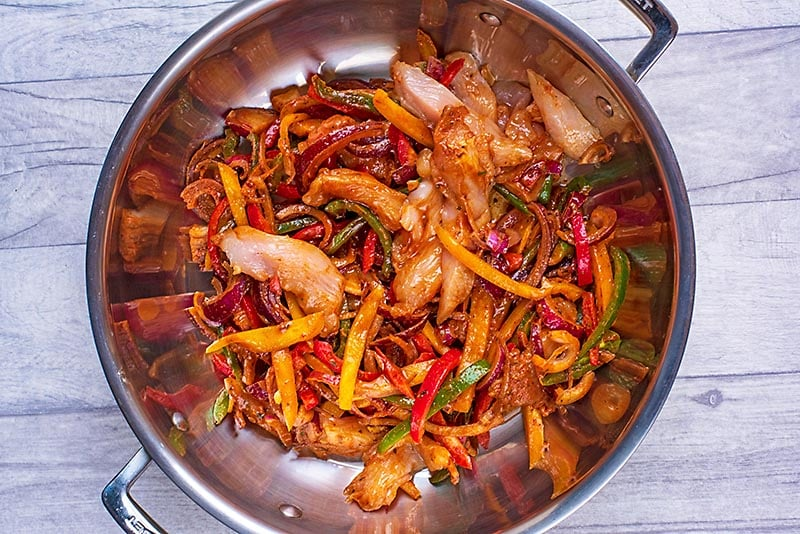 Raw marinated chicekn and strips of pepper and onion in a large pan