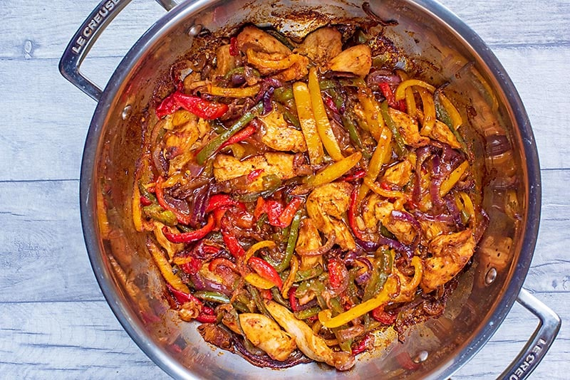 Cooked chicken, peppers and onions in a large silver pan