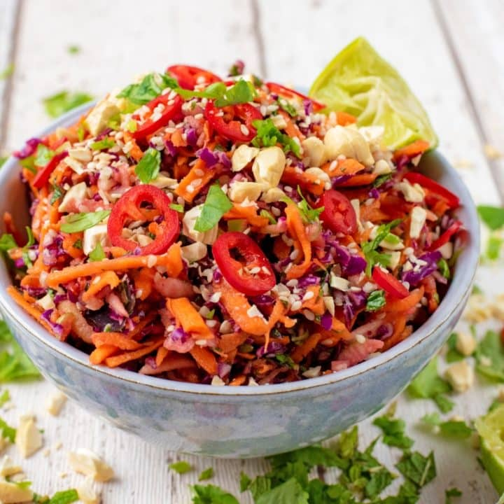 Asian Slaw in a blue bowl surrounded by sliced chillies and herbs