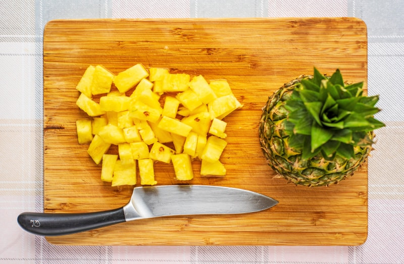 a wooden chopping board with a chef's knife, chunks of pineapple and a half whole pineapple