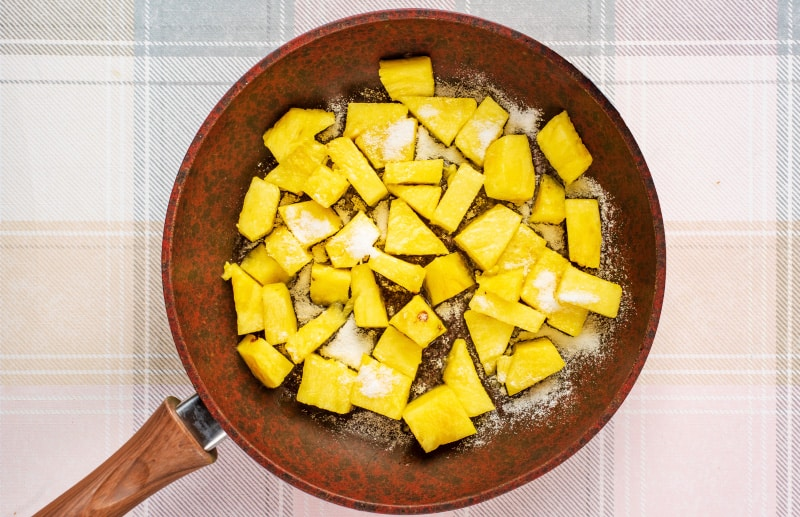 a frying pan containing chunks of pineapple and sugar