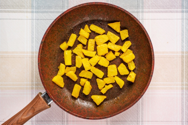 a frying pan containing chunks of cooked pineapple