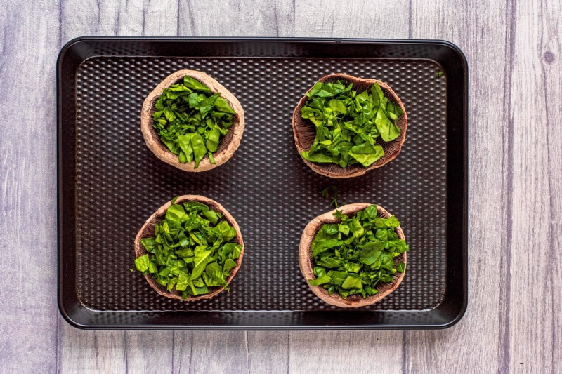 Four upturned portobello mushrooms topped with chopped spinach on a black baking tray