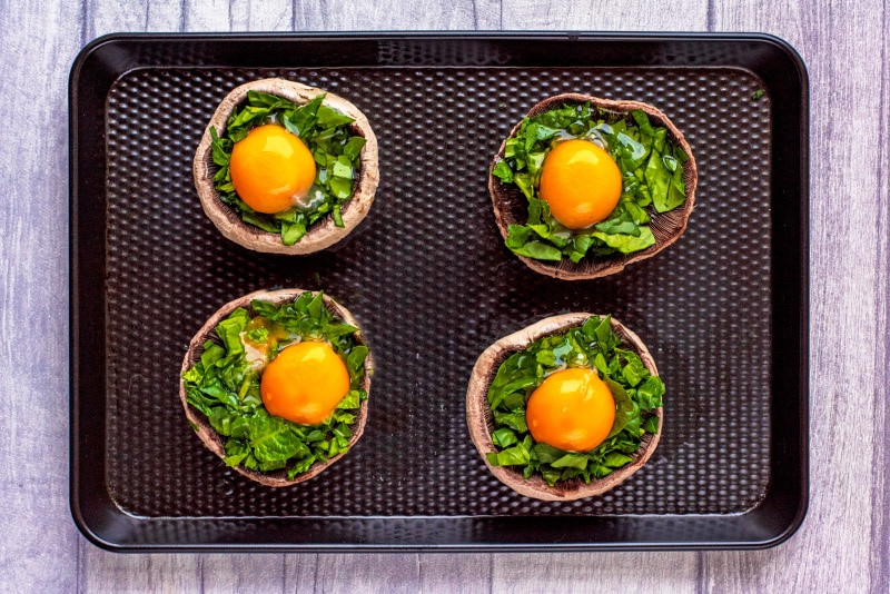 Four upturned portobello mushrooms topped with chopped spinach and a cracked egg on a black baking tray