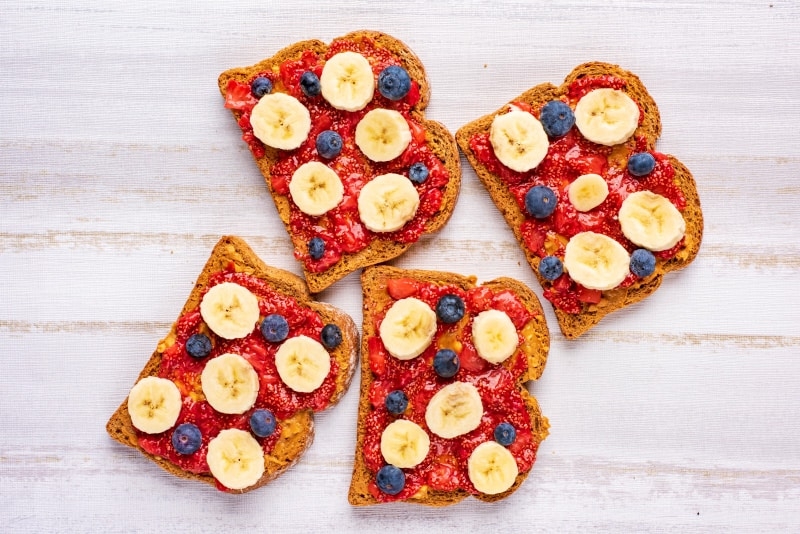 four slices of brown bread covered with peanut butter, strawberry jelly, banana slices and blueberries