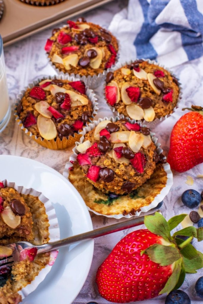 Four Banana Oat Muffins on a table next to another muffin on a plate