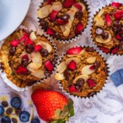 Four Banana Oat Muffins next to strawberries and a striped towel