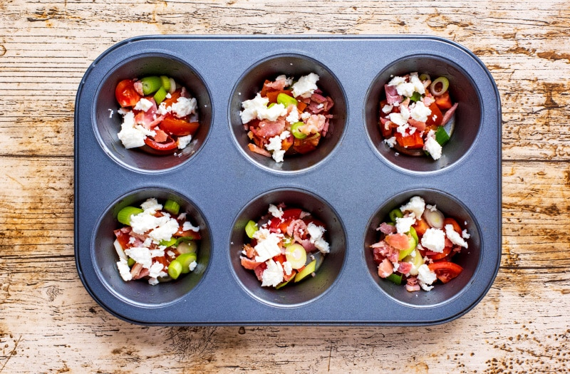 A six hole muffin tin with each hole containing dome red pepper, bacon, onion and cheese