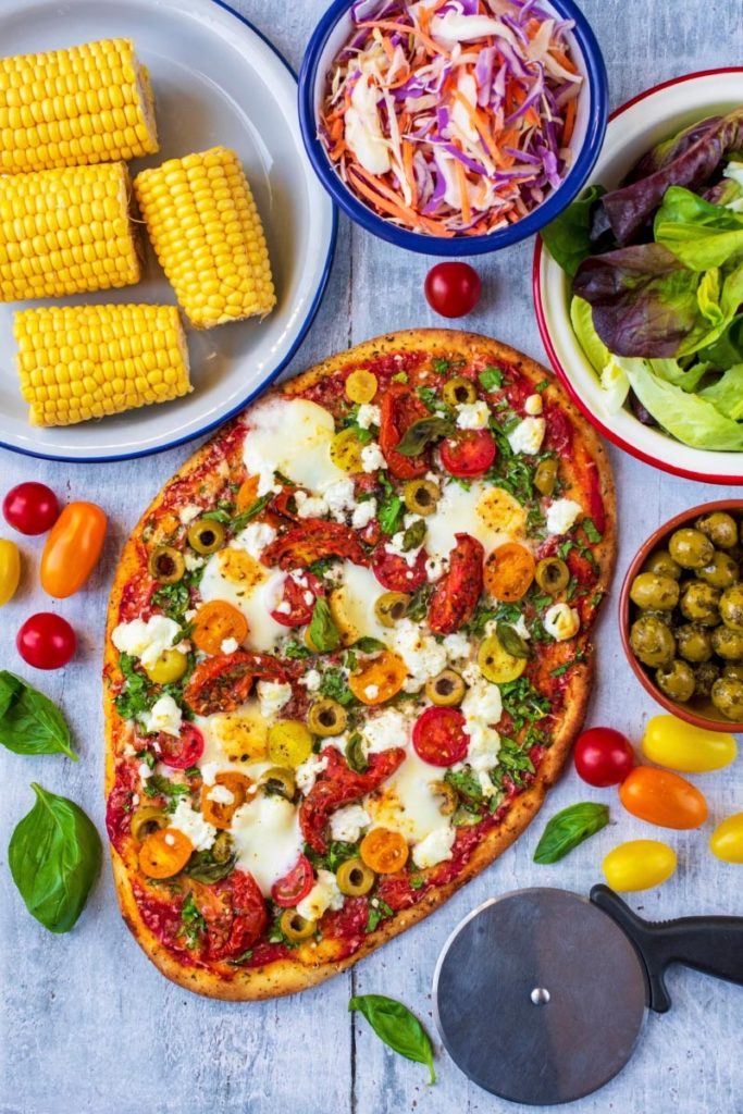 Easy Naan Pizza on a wooden surface next to a bowl of corn on the cob, some slaw and salad