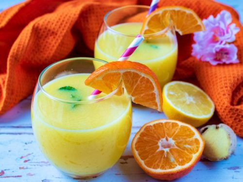 Two glasses of Immune Booster Juice next to orange and lemon halves