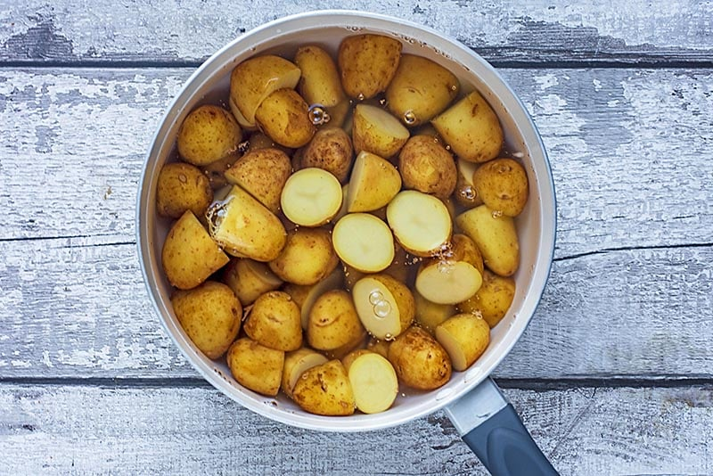 A saucepan with new potato halves in water