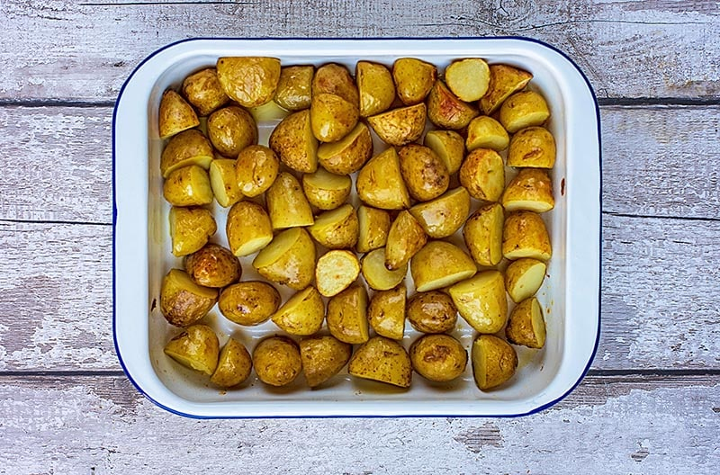 A baking tin containing cooked new potatoes