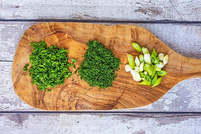 A wooden chopping board with chopped herbs an scallions on it