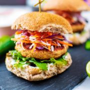 A salmon burger in a bun with lettuce and coleslaw