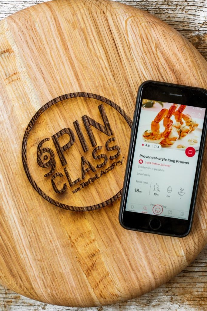 An iPhone on a circular chopping board showing the Tefal app