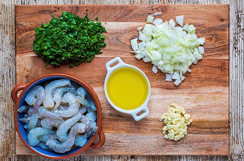 A wooden board with some prawns, oil and chopped onion, garlic and herbs