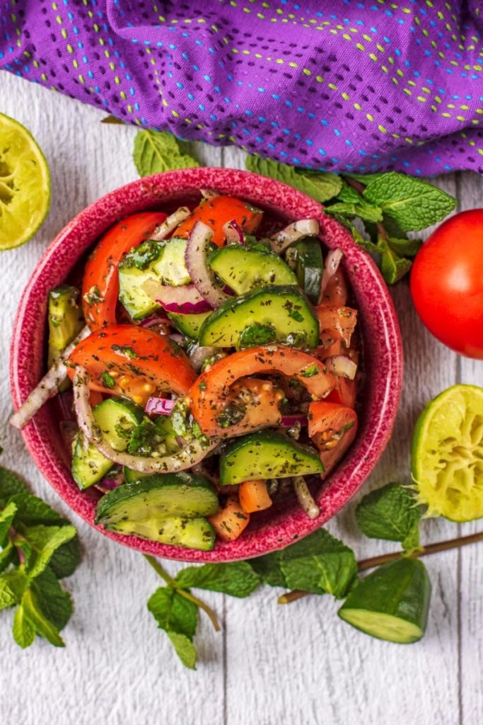 Cucumber Tomato Salad next to a purple towel on a wooden surface
